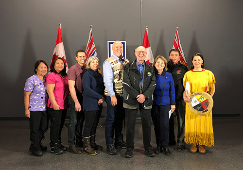 BC Premier John Horgan and Minister Dix posing with a group of people, there are official Canada and BC flags behind them.