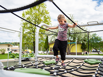 Young girl playing on rope net in playground at at Le Bourdais Park in Quesnel, BC.
