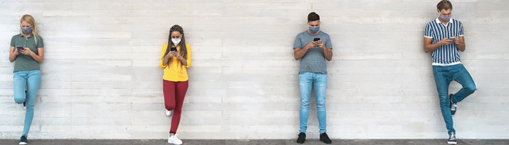Young people wearing surgical masks, using their smartphones while waiting in line and socially distancing.