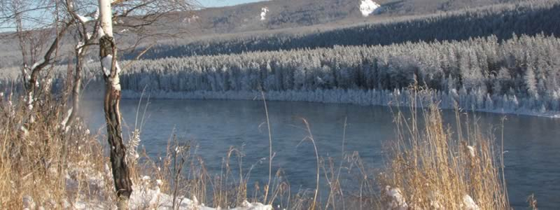Flowing river in the winter with snow covered trees on the banks.