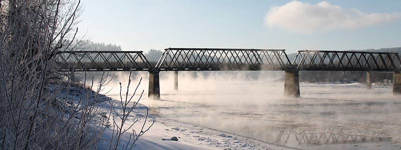 Train bridge with ice fog coming off the river in winter.