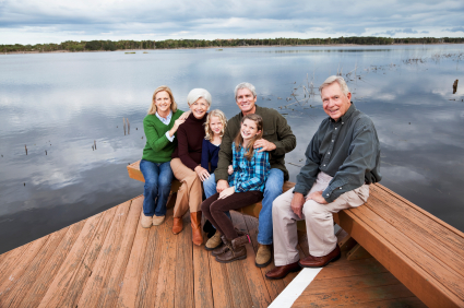 Generational family sitting on a dock by a lake