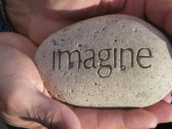 The word IMAGINE is etched into a smooth round stone